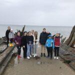 Участники лагеря на берегу моря у остова старого корабля