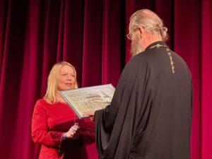леся Балакирева вручает отцу Виктору Мельнику подарок к юбилею храма